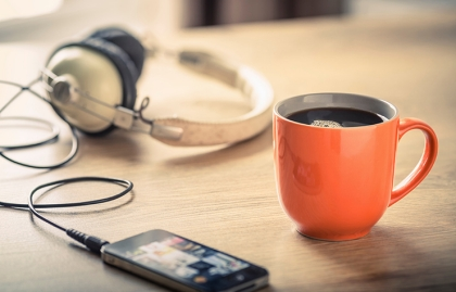 Café en una una taza color naranja al lado de un teléfono celular y unos audífonos