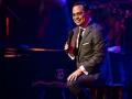 Gilberto Santa Rosa sentado frente a un piano en un concierto