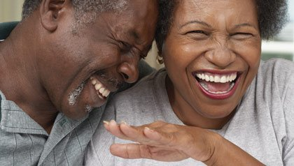 Mature couple laughing - good news websites share positive news over doom and gloom