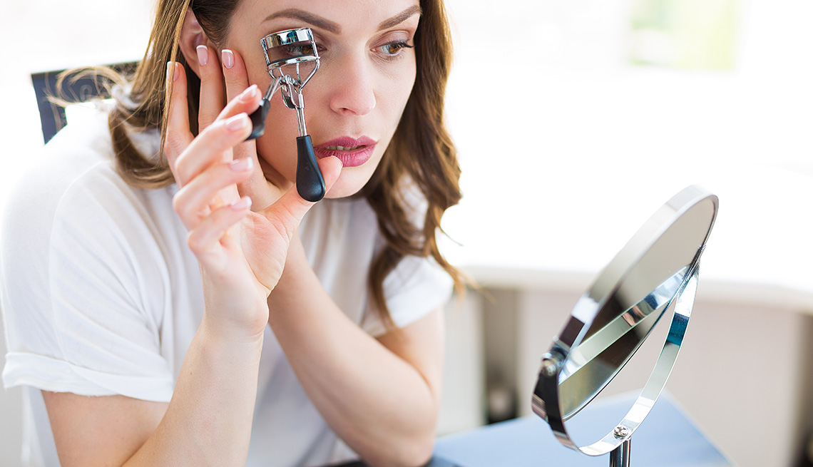 Use and eyelash curler and a magnifying mirror
