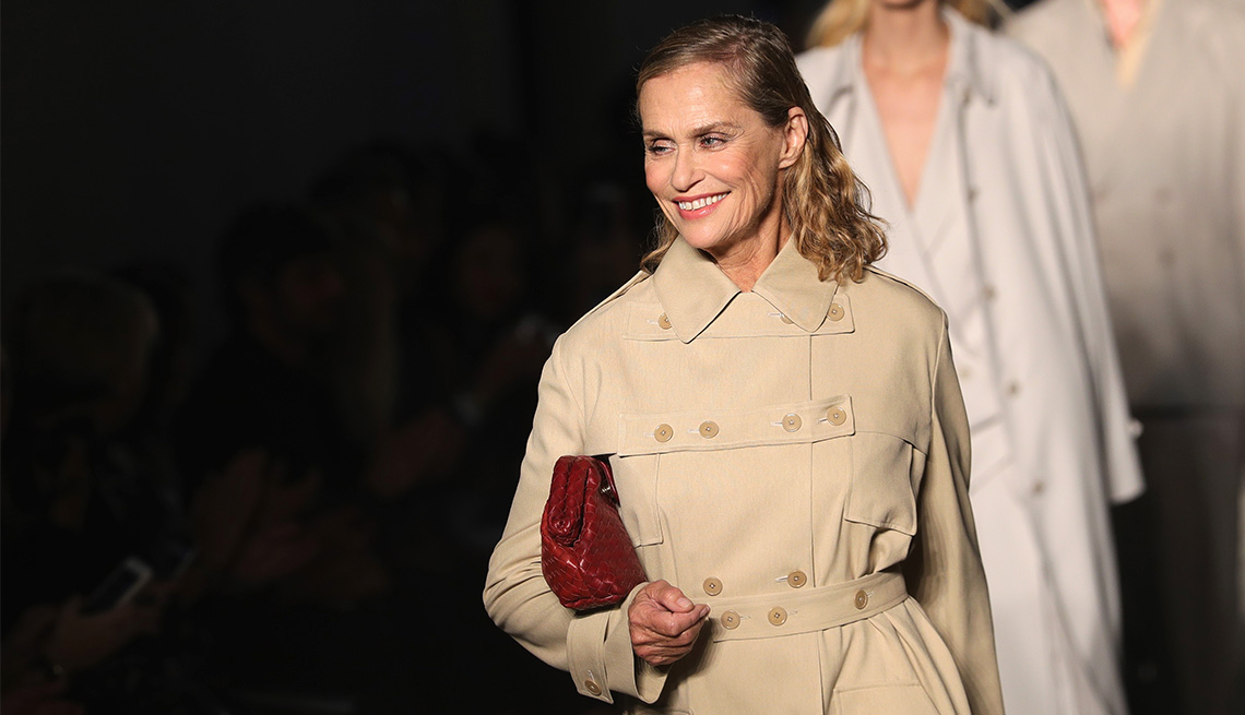 Model Lauren Hutton smiling while holding a purse and wearing a beige trench coat.