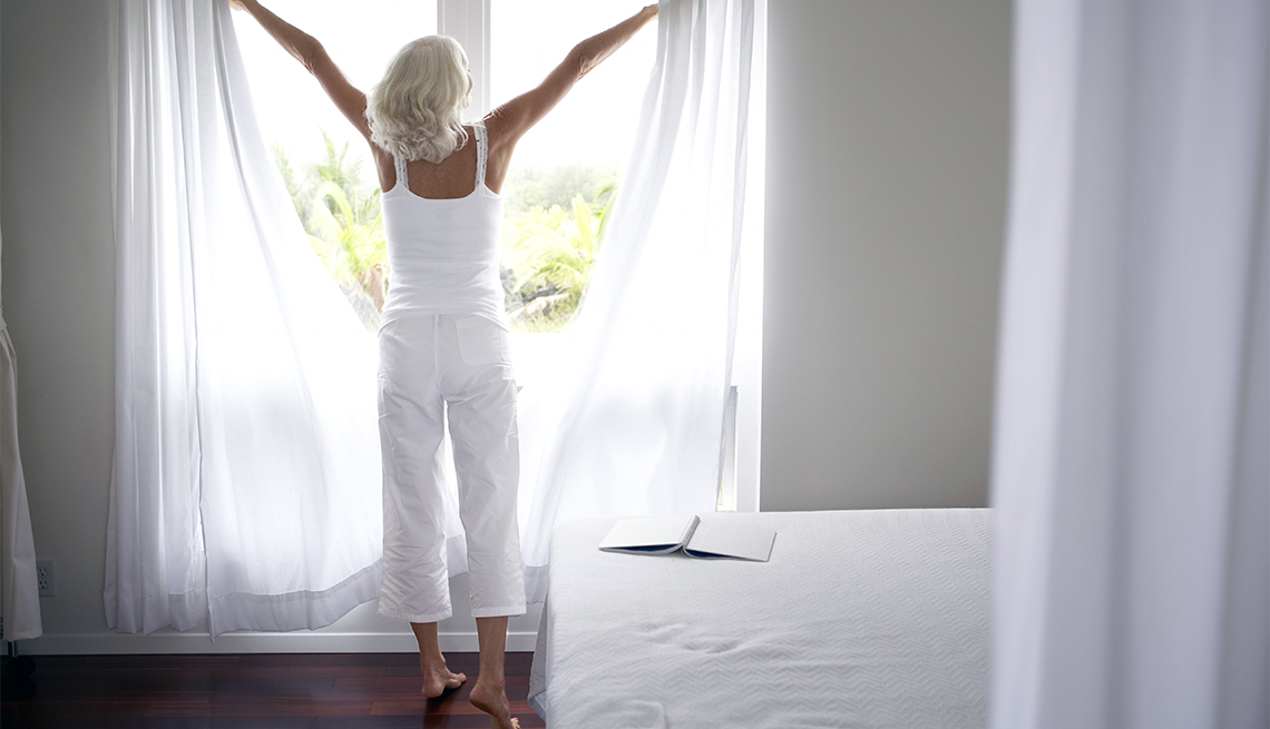 A mature women pushes drapes aside to look out her bedroom window.