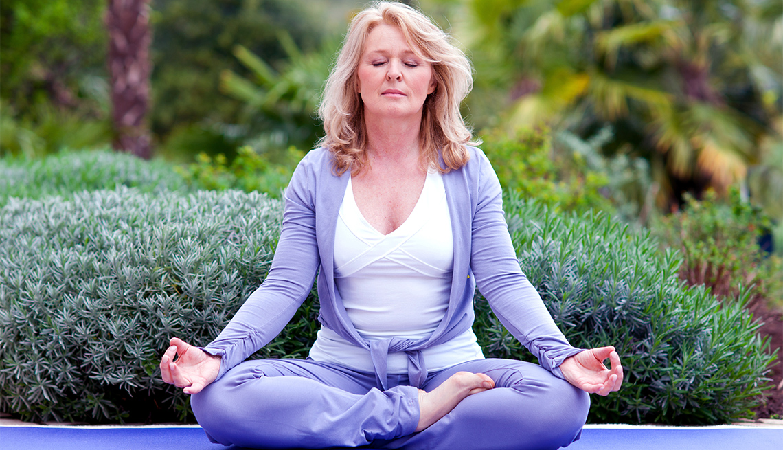 A women meditates in lotus position surrounded by an outdoor garden.