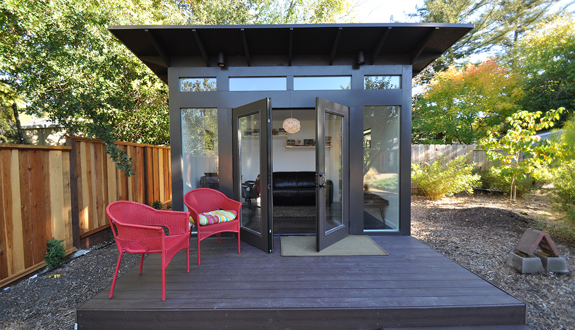 An outdoor studio shed designed for comfort living in a fenced backyard.