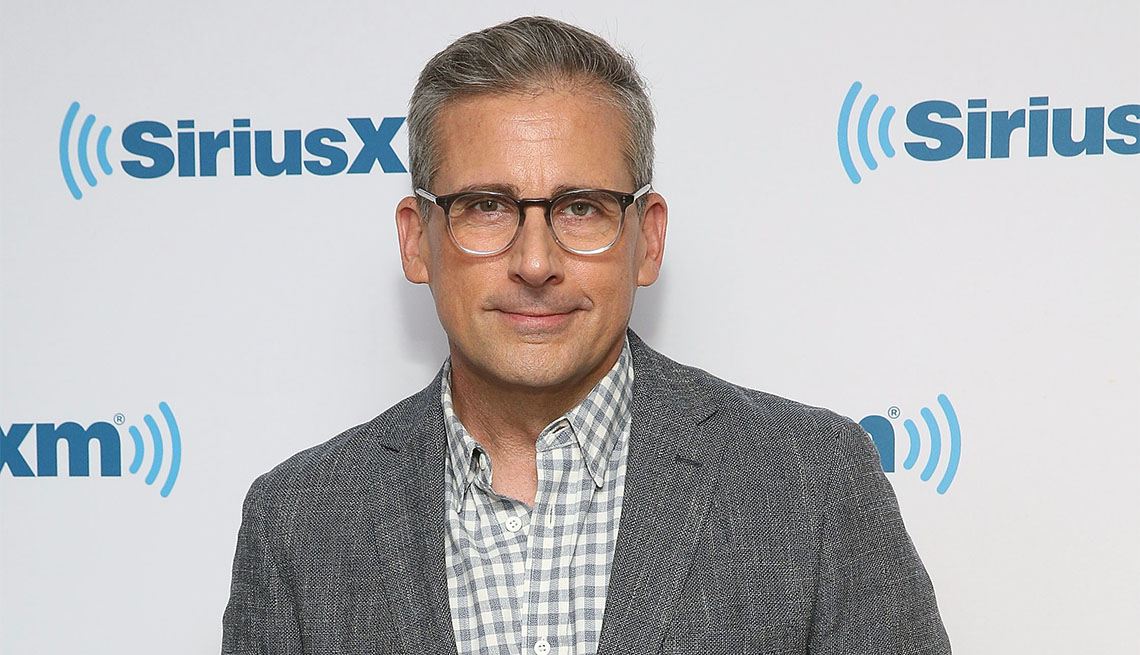 Actor Steve Carell wearing a gray blazer and checkered shirt.