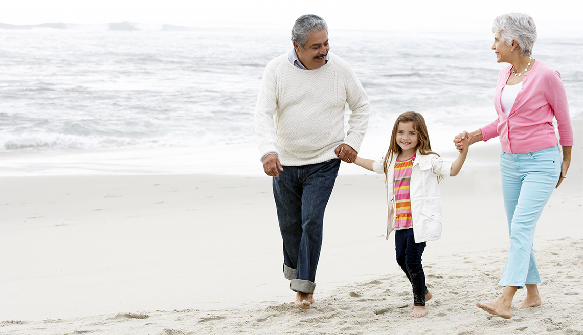 Grandparents walking on a beach while holding their granddaughter's hand.