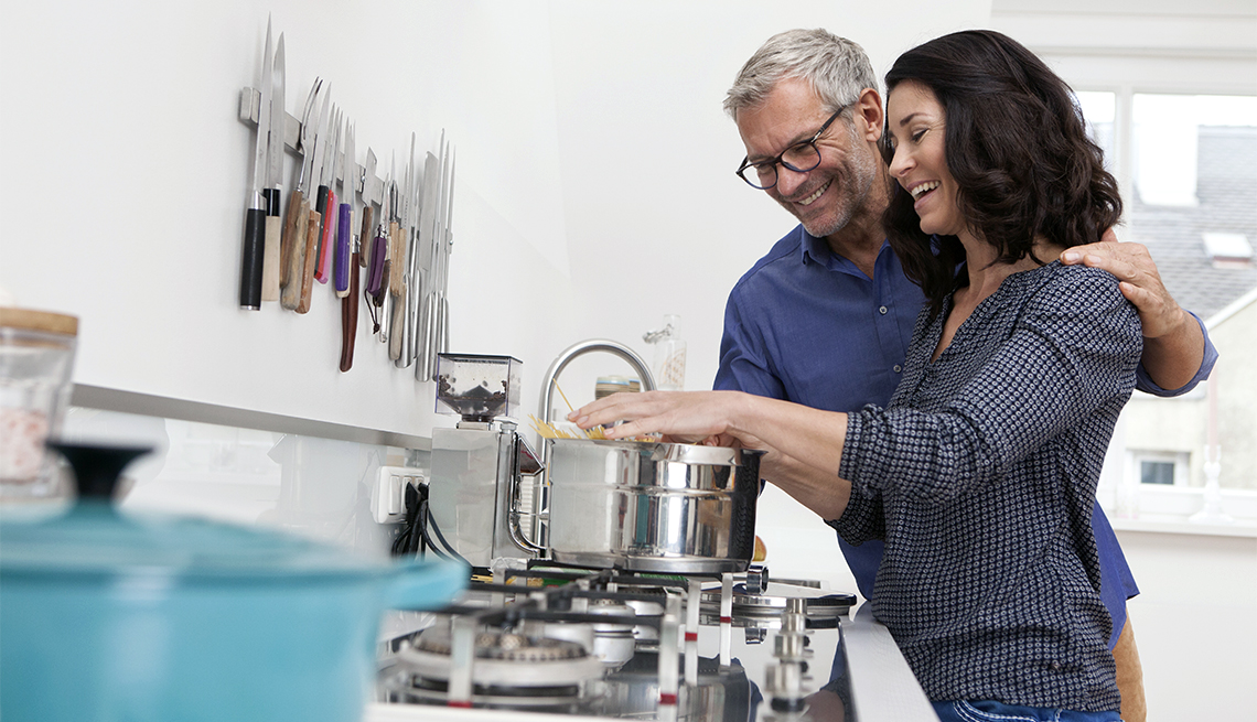 A happy, mature couple cooks together in a kitchen.