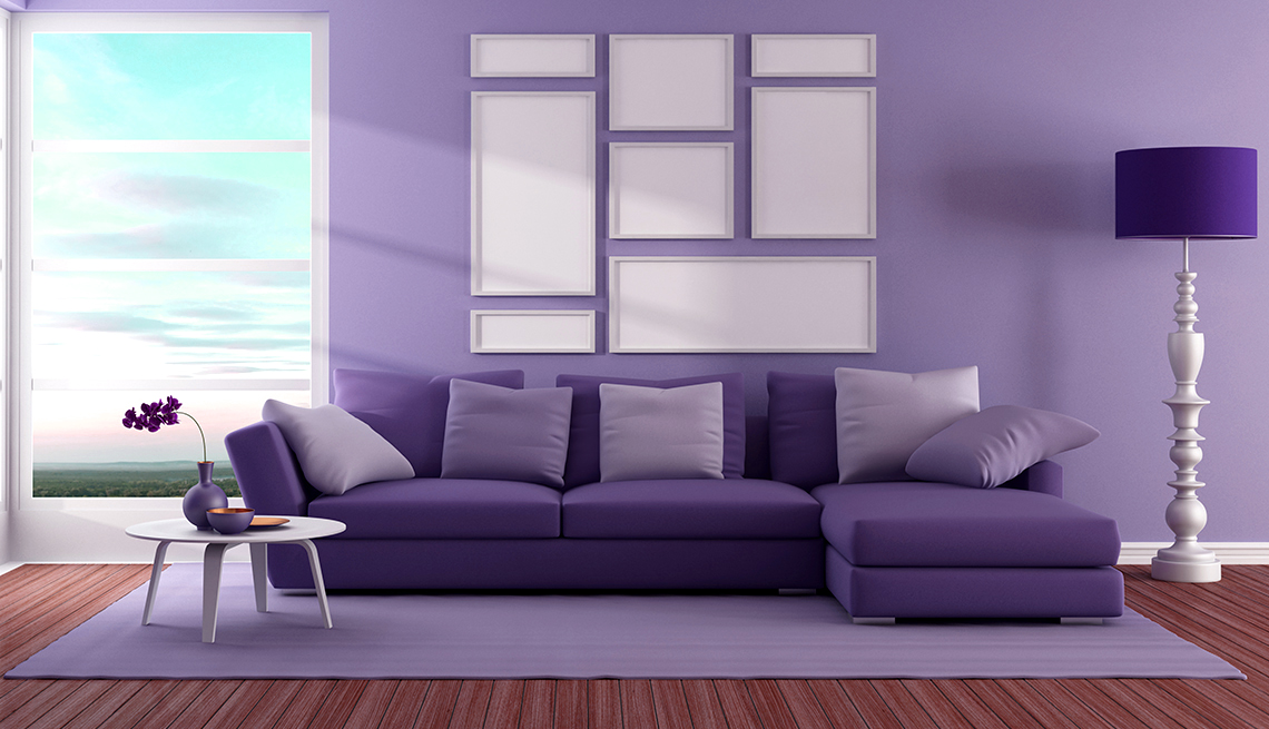 A living room with a purple carpet, purple couch, purple lampshade, and walls painted purple.