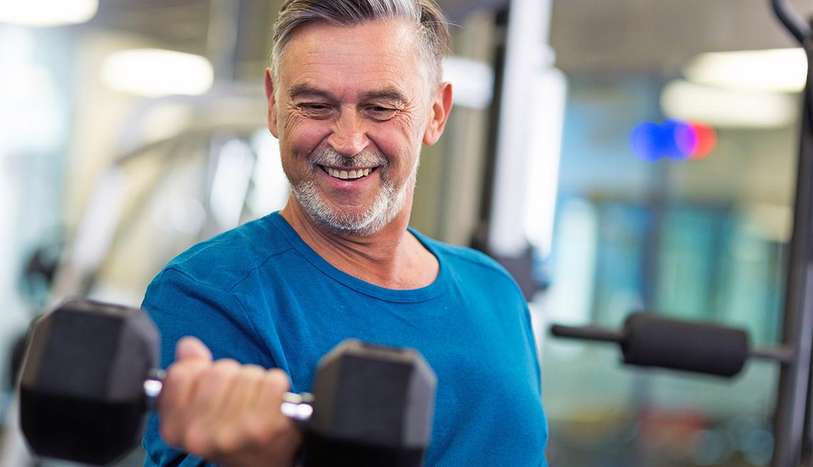 A fit, mature man wearing a blue shirt curls a dumbbell at a gym.