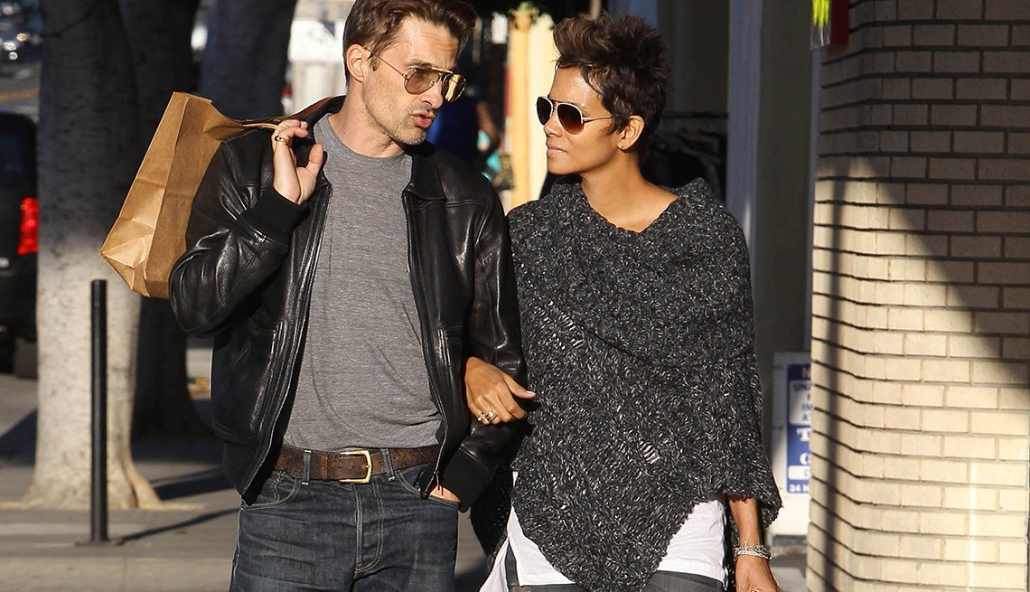 item 12 of Gallery image - Halle Berry wearing a gray poncho sweater, walks down a sidewalk with friend