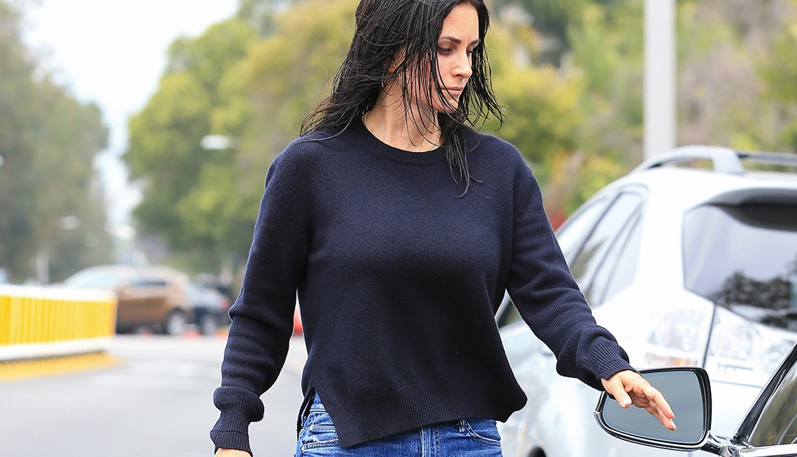 item 11, Gallery image. Actress Courteney Cox spotted in a black crew neck sweater with side vents in June 2017.