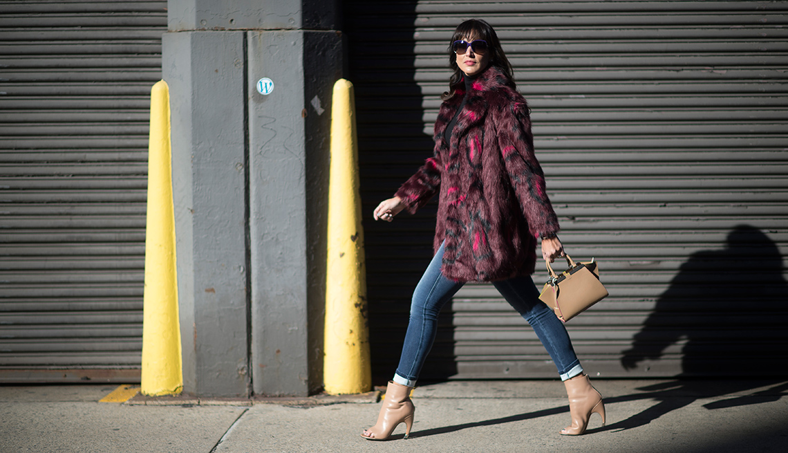 Woman walking on sidewalk in light, maroon and black coat, jean leggings, tan shoes and purse