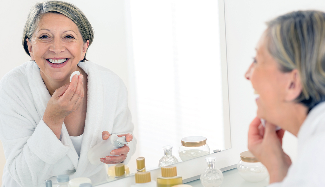 Mature woman looks in mirror, smiling, and applies makeup.