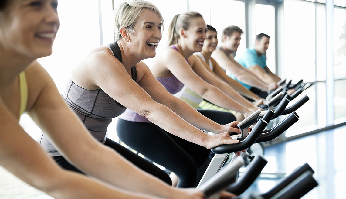 A row of women riding stationary bikes at a gym.