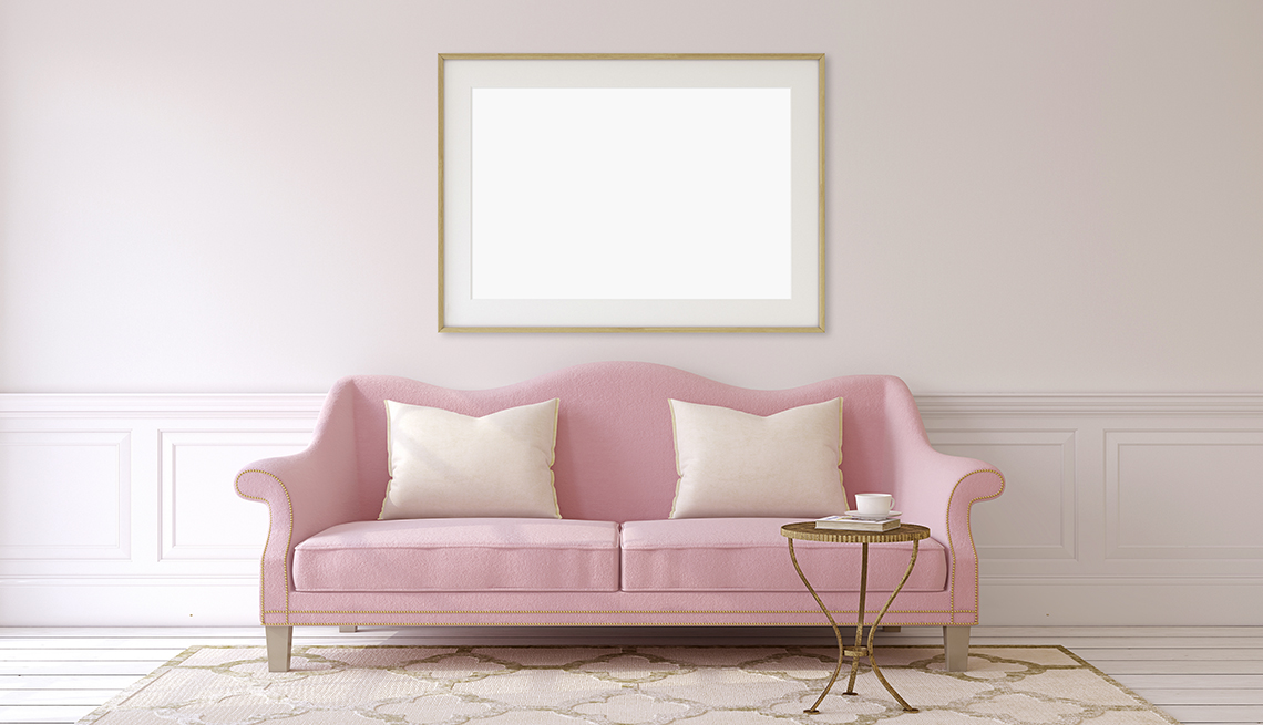 An interior living room painted pink, including a mirror, couch, pillows, and end table.