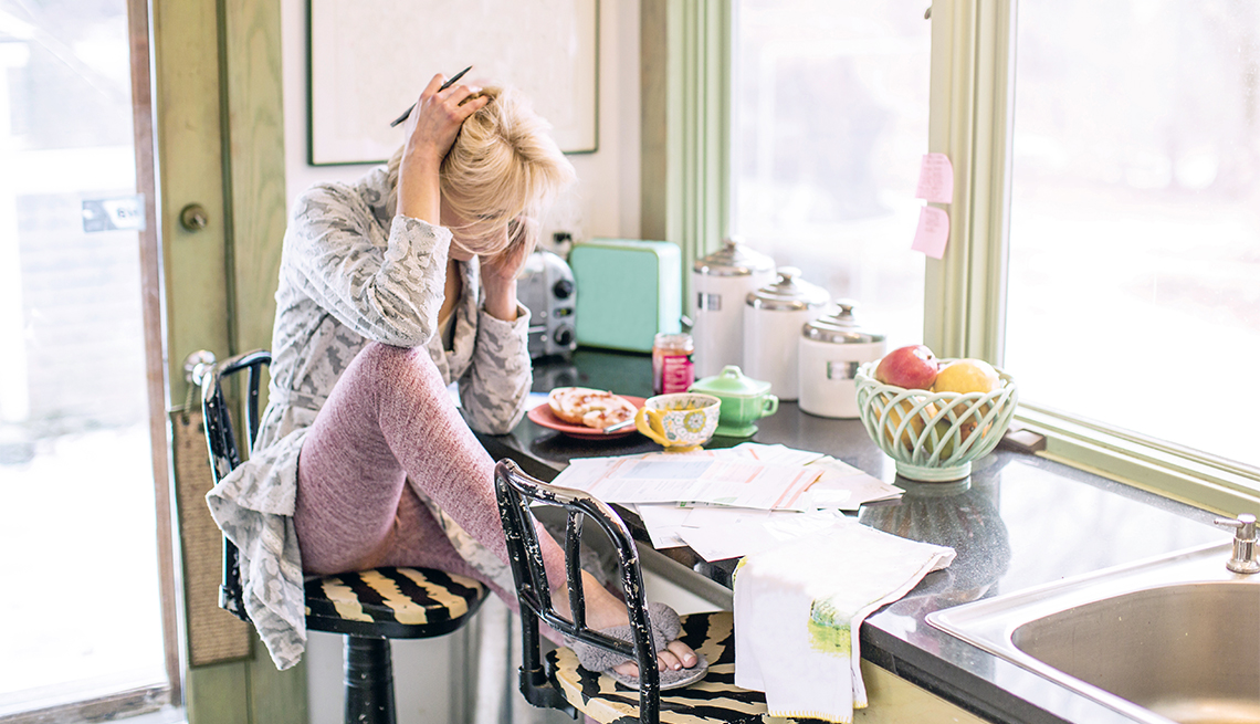 A women multitasks at her kitchen counter.