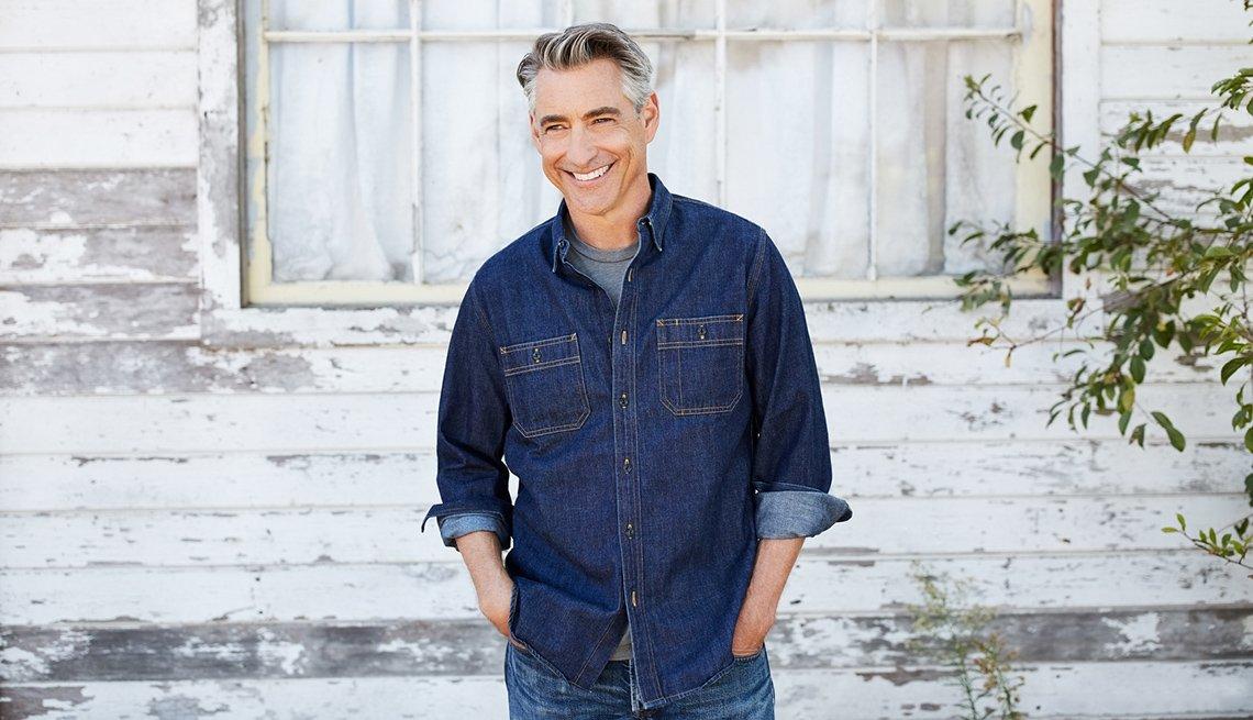 Hombre sonriendo y usando una camisa de jean.