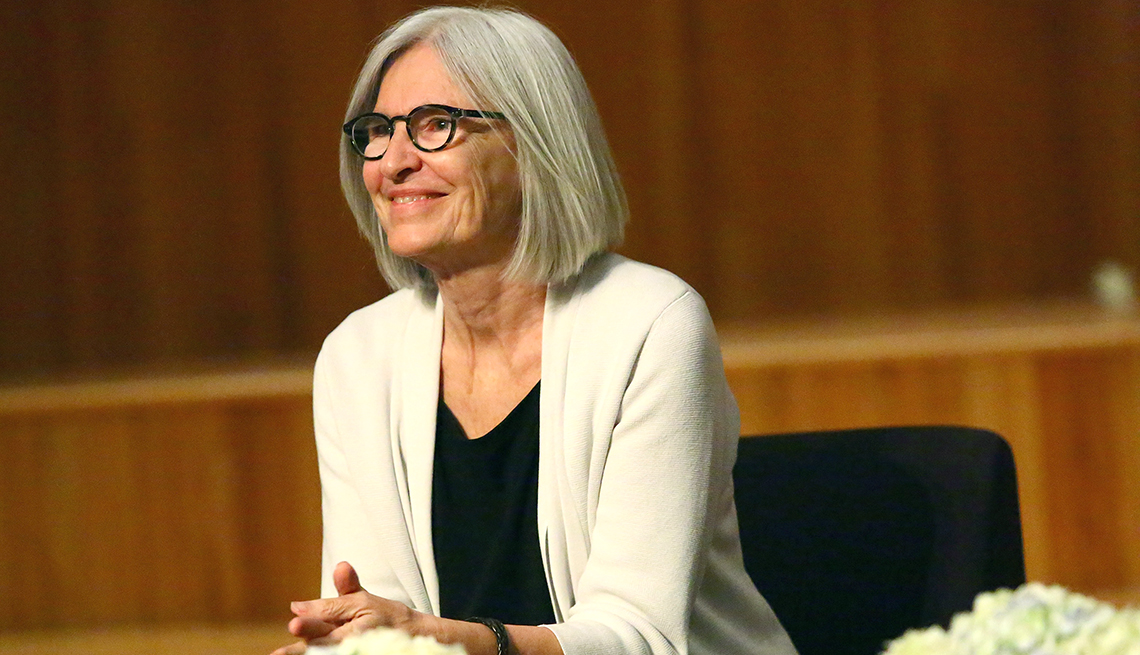 Fashion designer Eileen Fisher seated on a stage with wood paneling