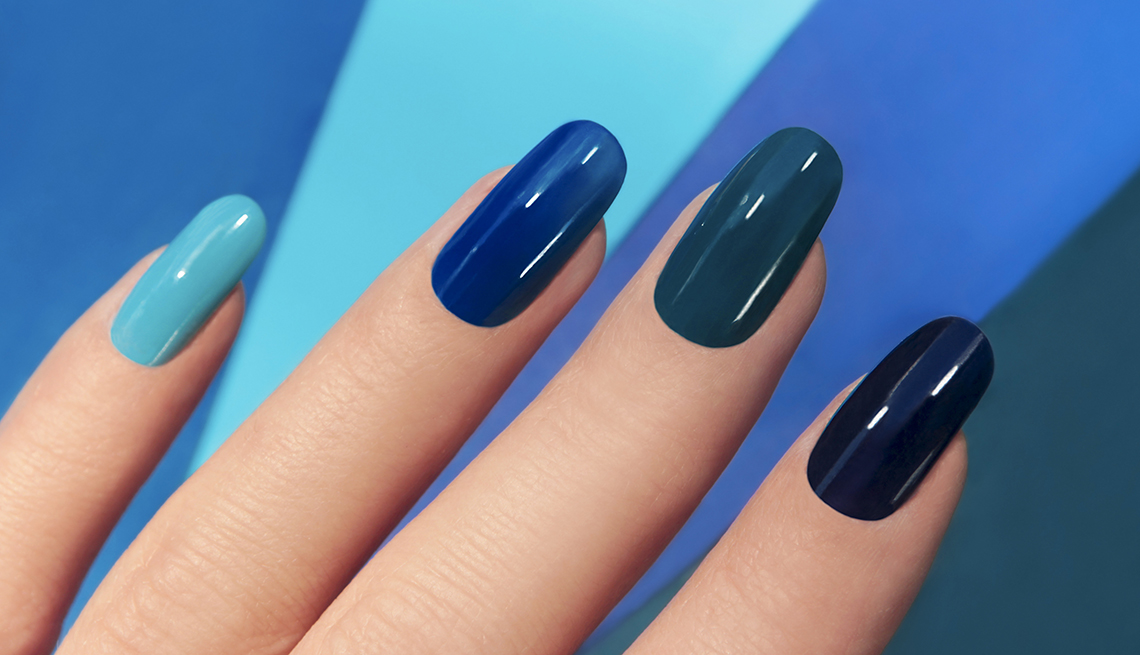 Blue manicure in light and dark colors of lacquer on a striped background