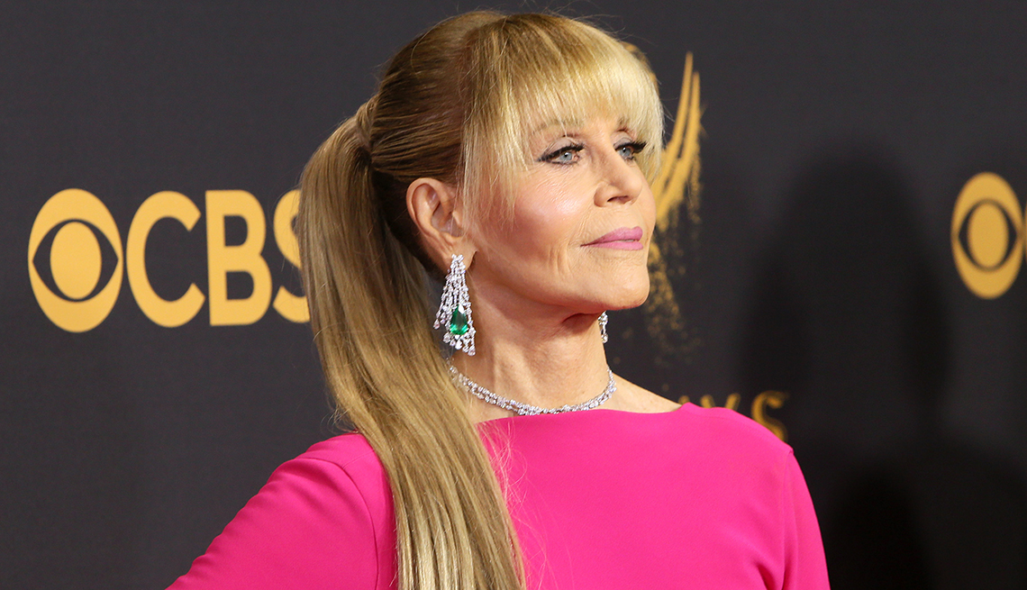 actress jane fonda on the red carpet, wearing bright pink with hair in ponytail