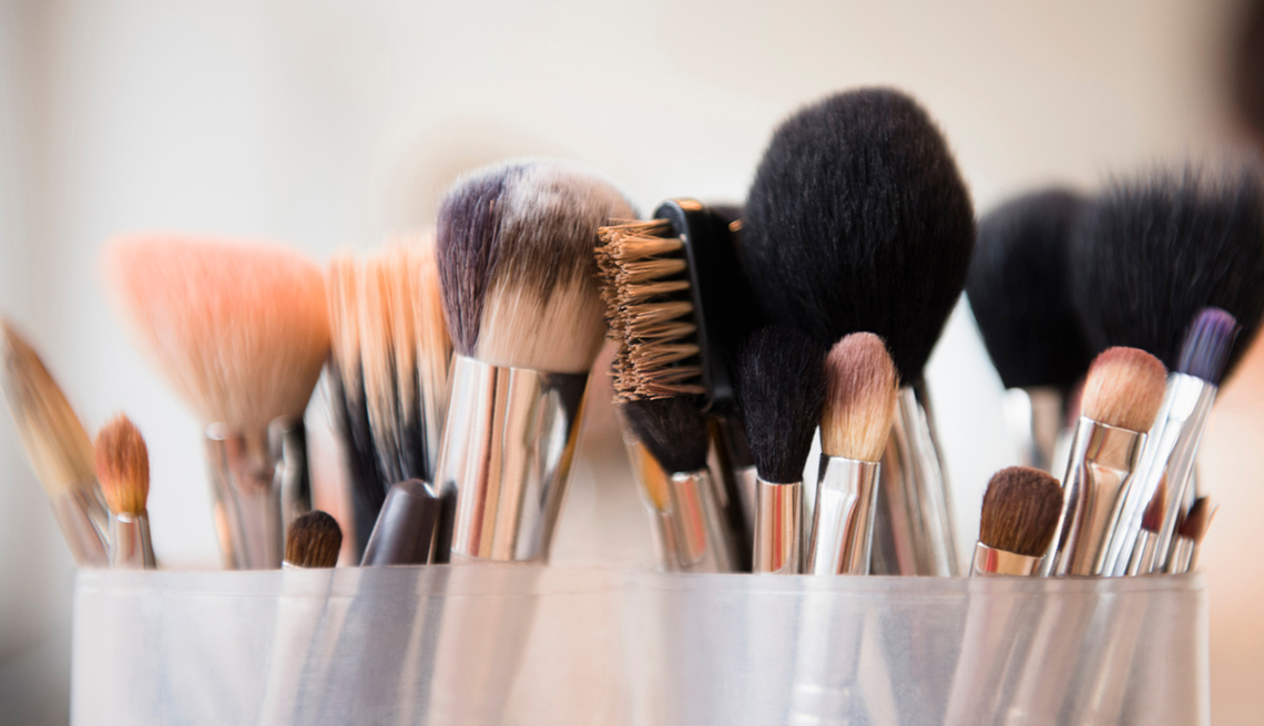 various makeup brushes in clear cups