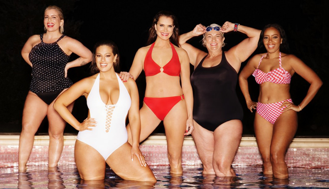 5 woman wearing swimsuits and standing with their feet in water.