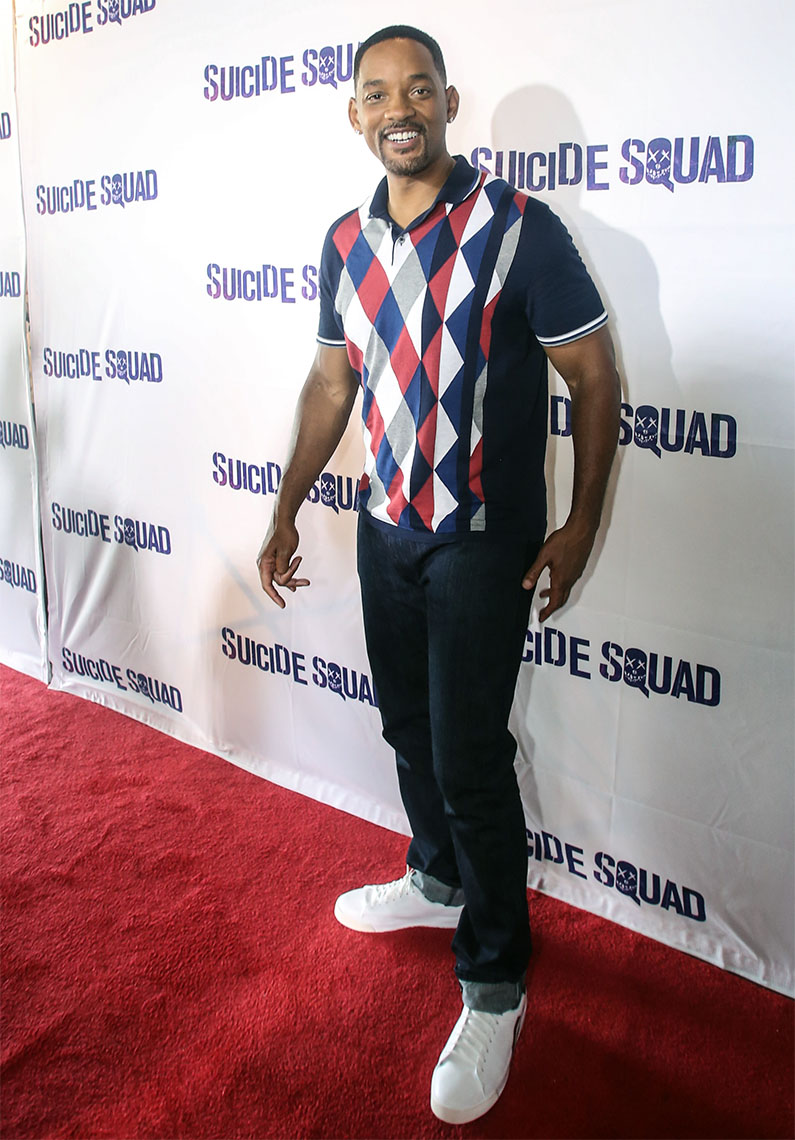 Will Smith on the red carpet wearing a colorful untucked polo with jeans and white sneakers