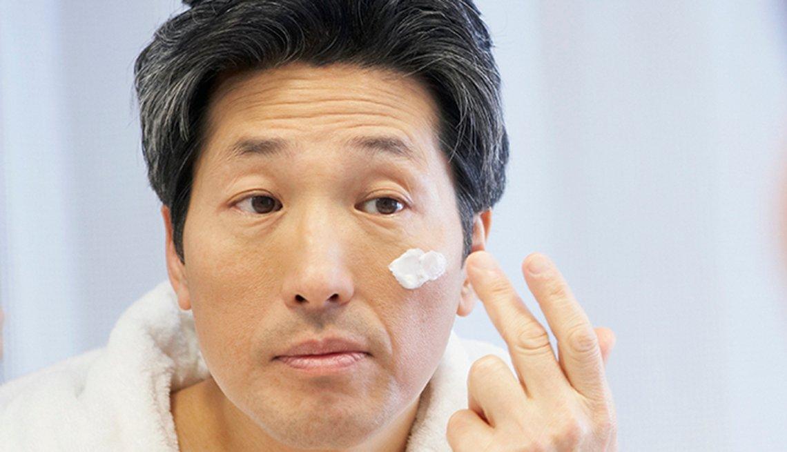 Hombre colocándose crema en la cara