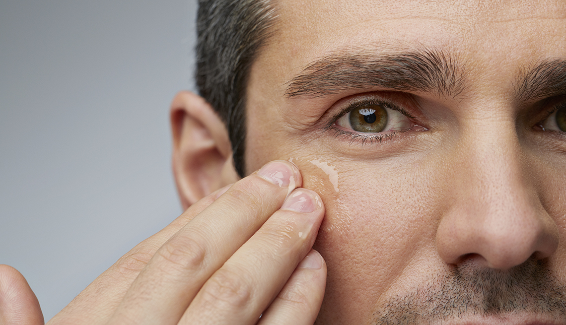 Man rubbing clear cream under his eyes.