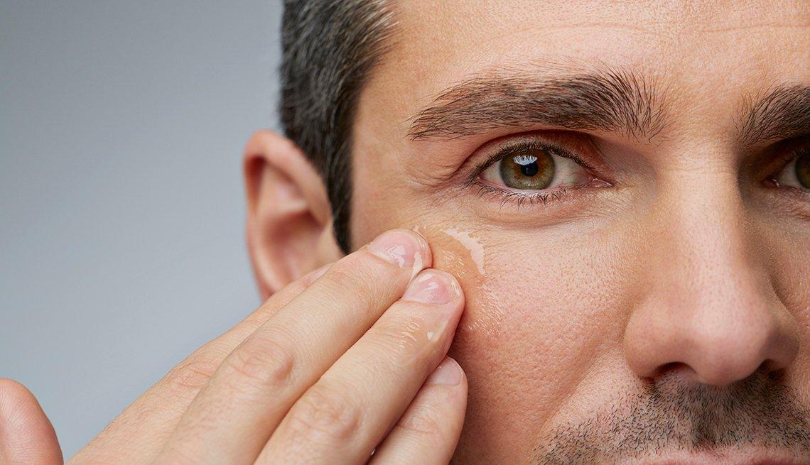 Man rubbing clear cream under his eyes.