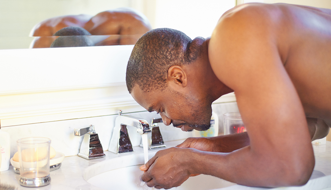 Man leaning over a bathroom sick washing his face