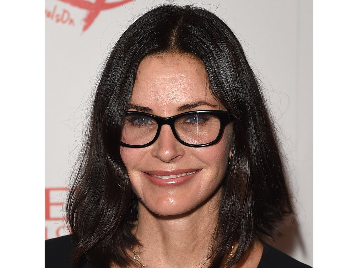 Courteney Cox wearing black frame glasses.