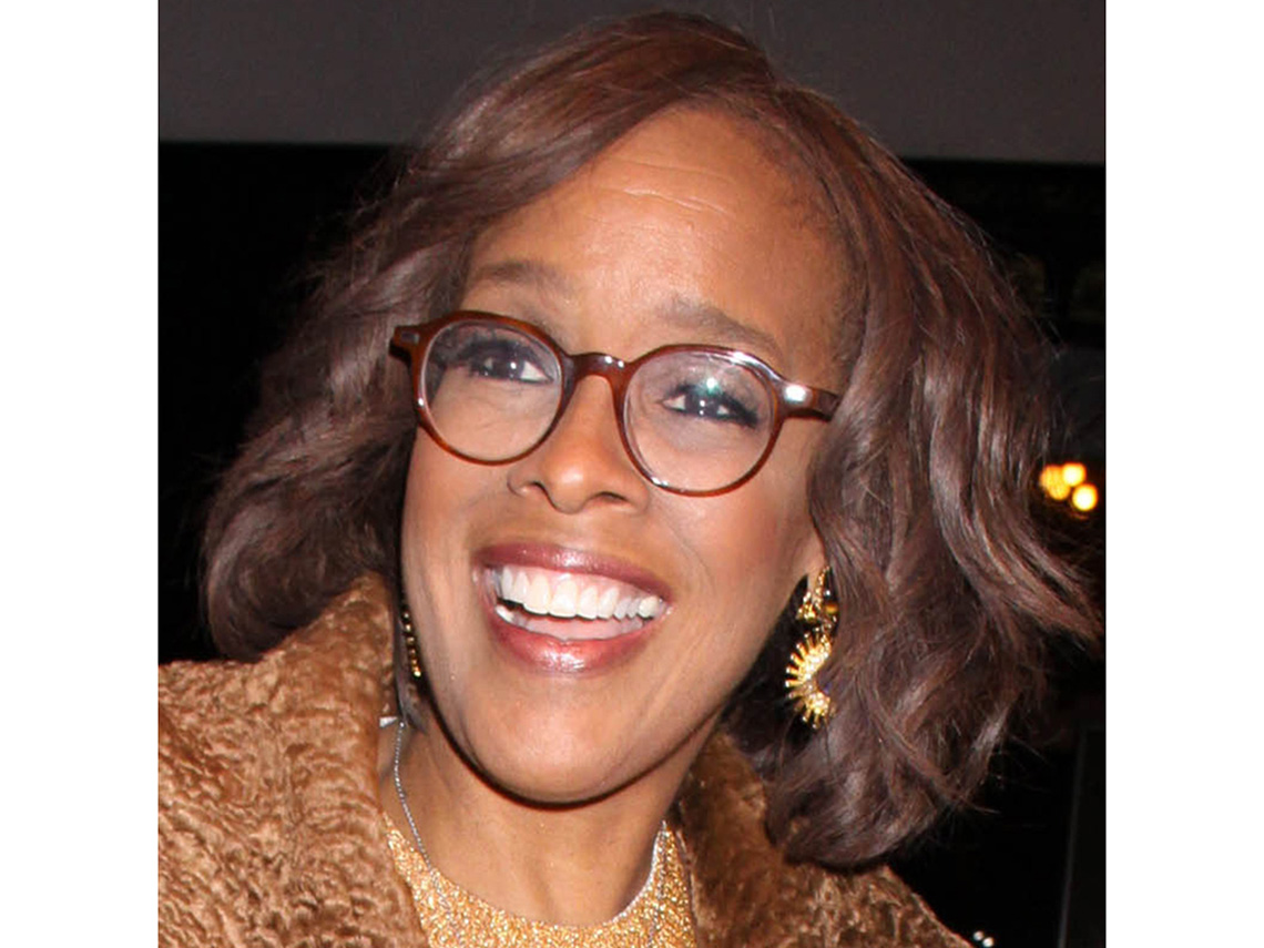 Gayle King in large thin burgundy frame glasses.