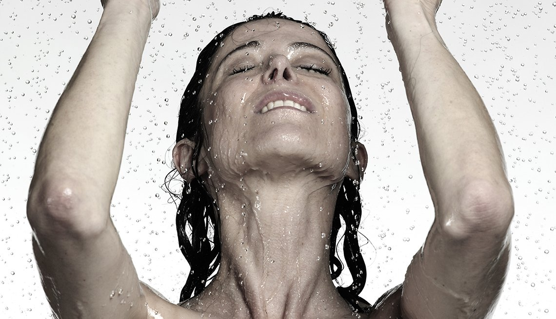 Mujer con los ojos cerrados y los brazos levantados mientras le cae agua.