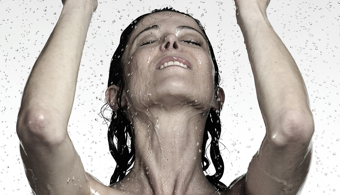 A woman standing in shower with water coming down on her face.