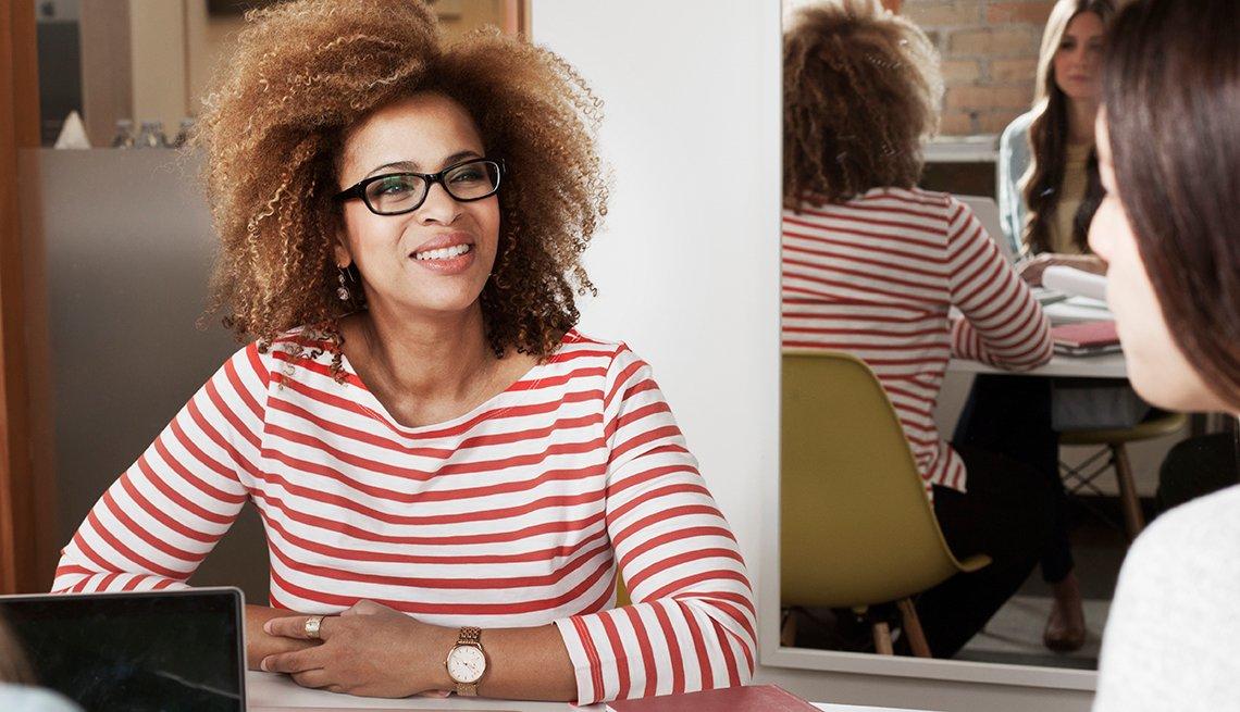 Mujer ejecutiva hablando en un salón con otras personas alrededor de una mesa