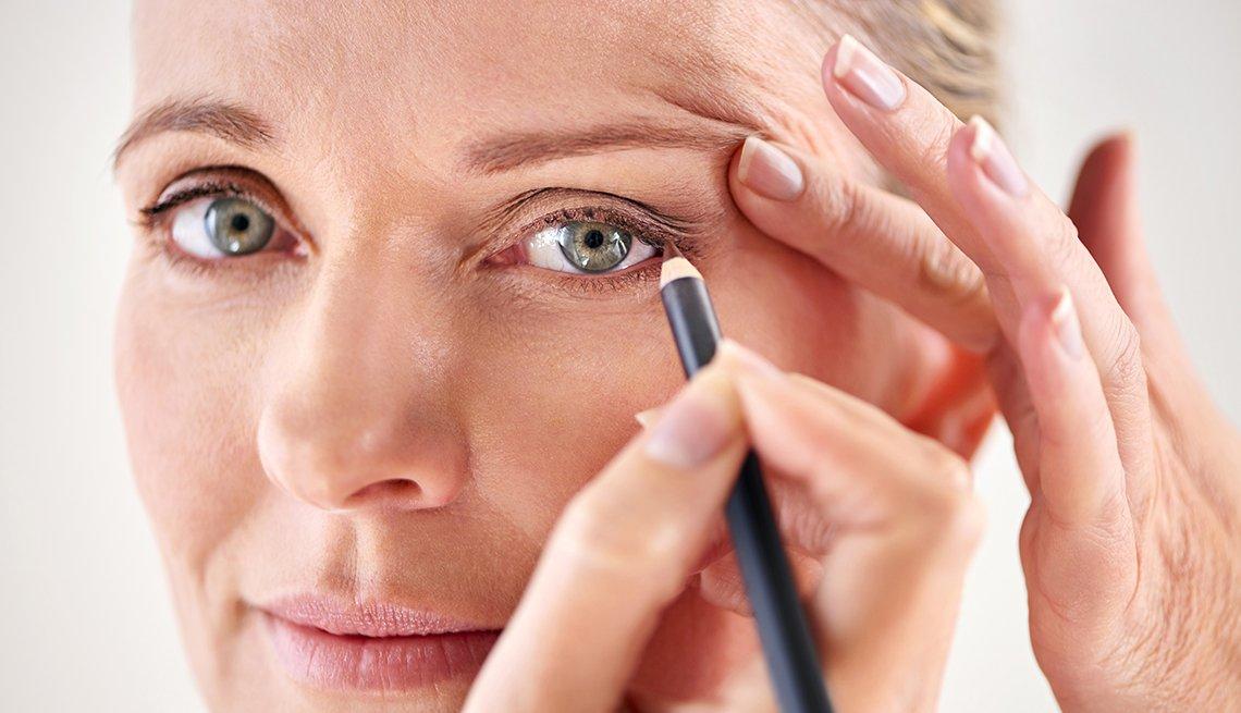 Mujer usando un lápiz para delinear los ojos