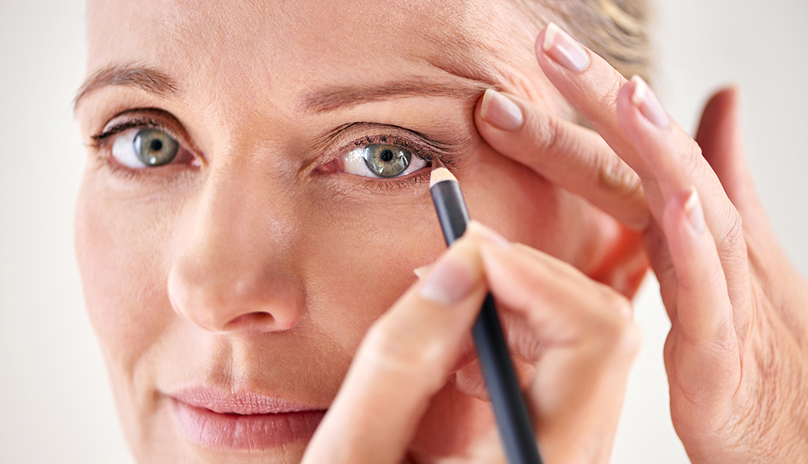 A woman applying eyeliner