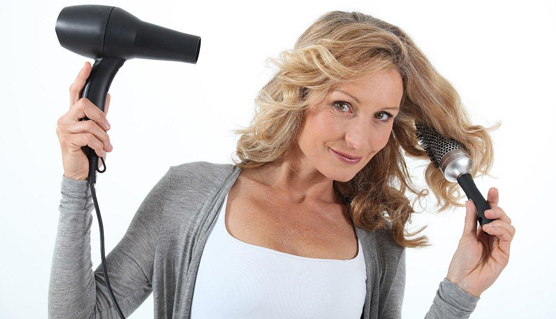 Mujer con secador y cepillo de pelo en las manos