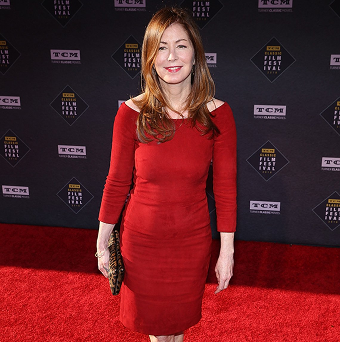 Dana Delany in a red nearly-off-shoulder knee-length sheath with 3/4 sleeves.