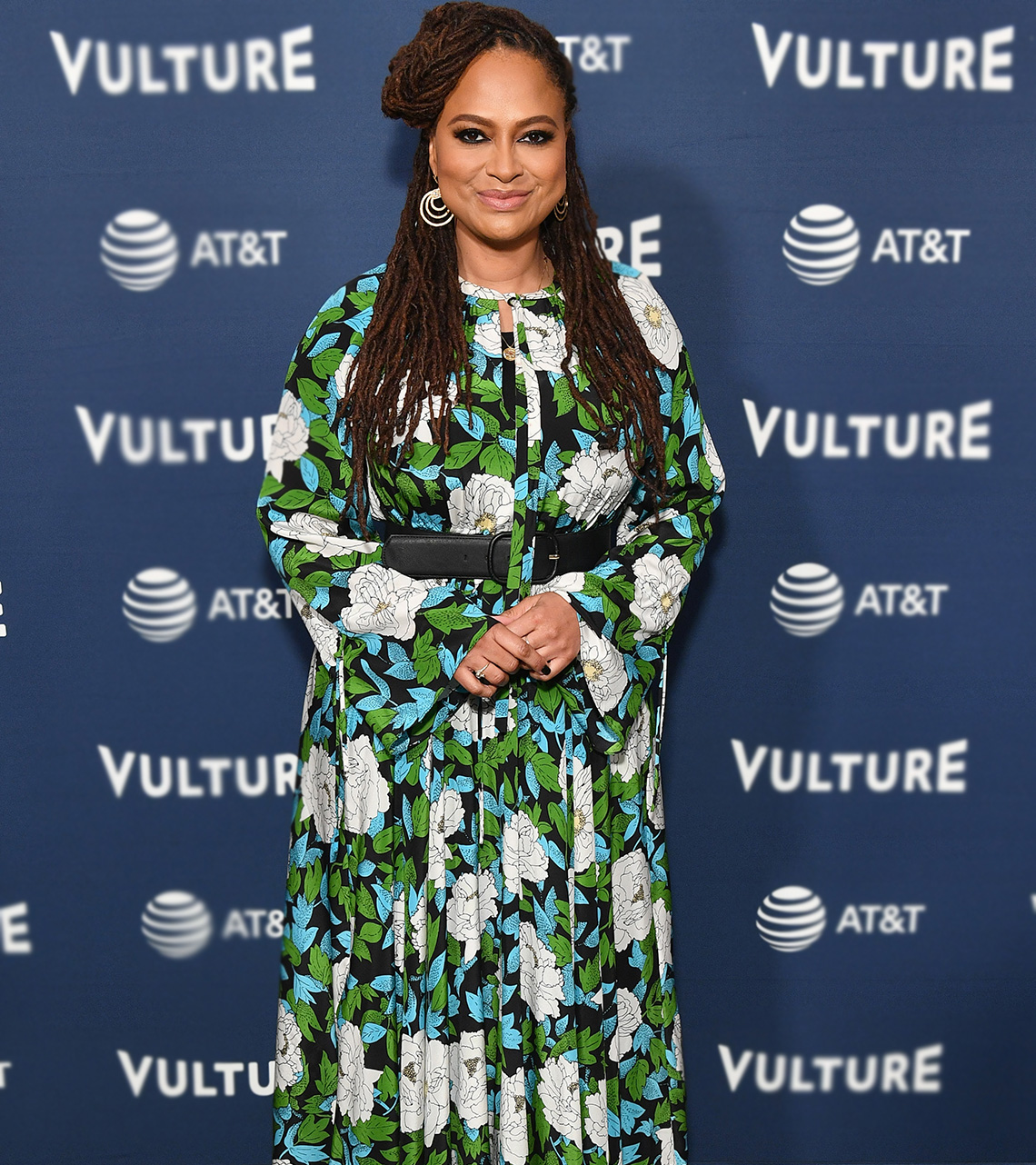 Ava DuVernay in a long flowing print dress with defined waist and bell sleeves.