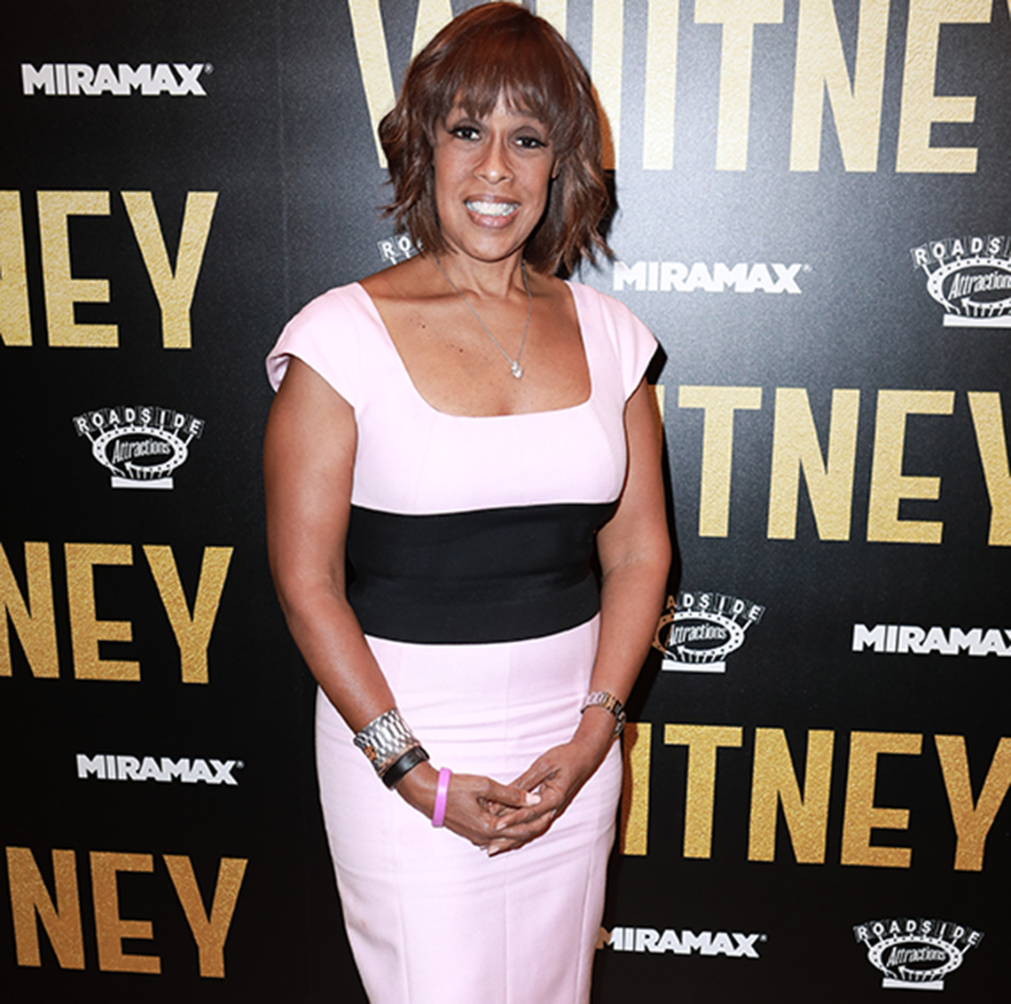 Gayle King in a color-block dress — square neck, cap sleeves, wide black midsection bust to top of hip.