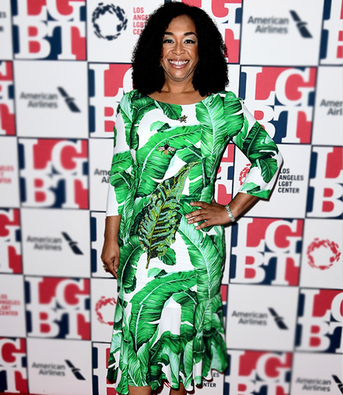 Shonda Rhimes in green-and-white leaf print dress with boatneck, 3/4 sleeves and ruffle hem.