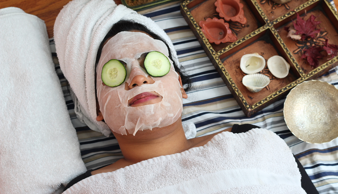 woman with sheet mask on face and cucumbers on eyes