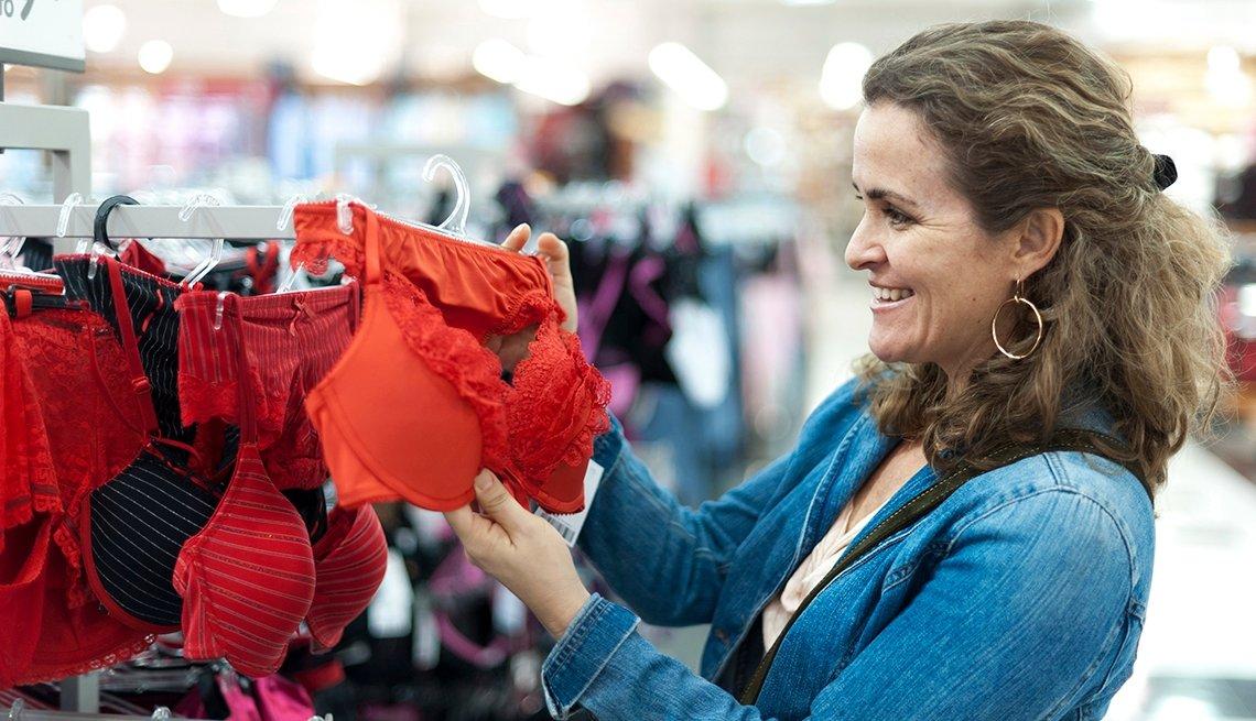 Mujer en una tienda de ropa interior con un sostén en las manos.