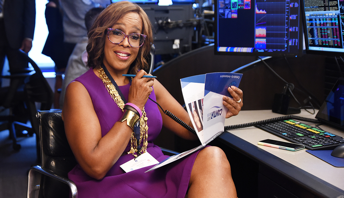 Gayle King event in a sleeveless purple dress, gold necklaces and purple multi-tone glasses