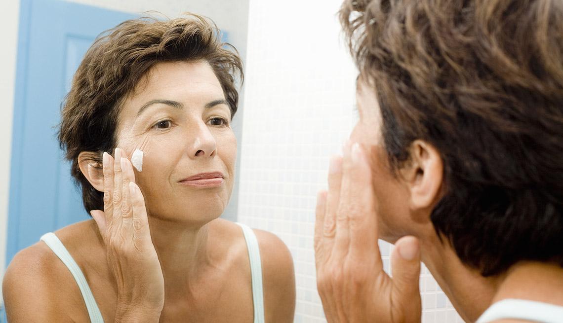 woman applying eye cream in mirror