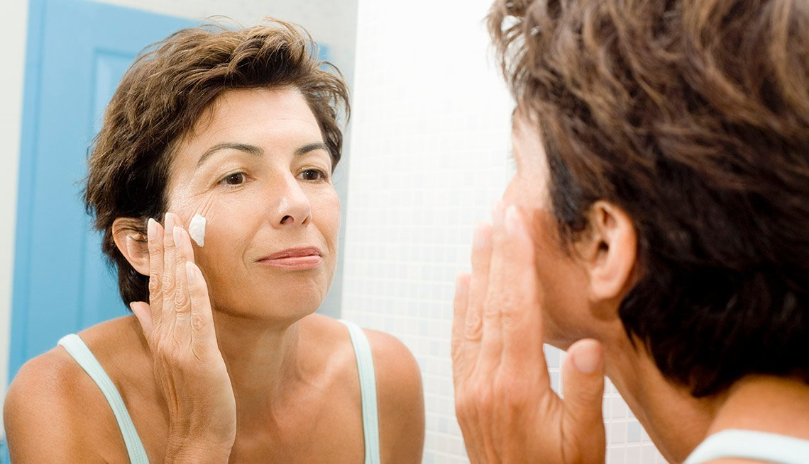 woman applying eye cream in mirror