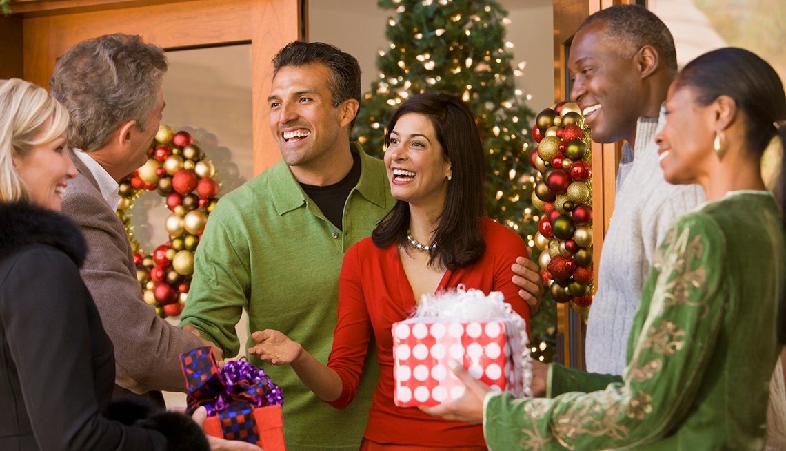 A group of people gathered for a holiday party, dressed casually in solid colors.
