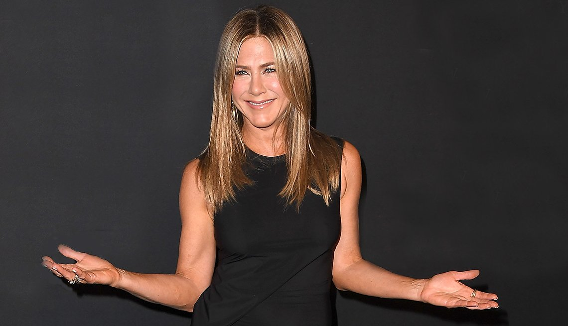 Jennifer Aniston holding her arms up